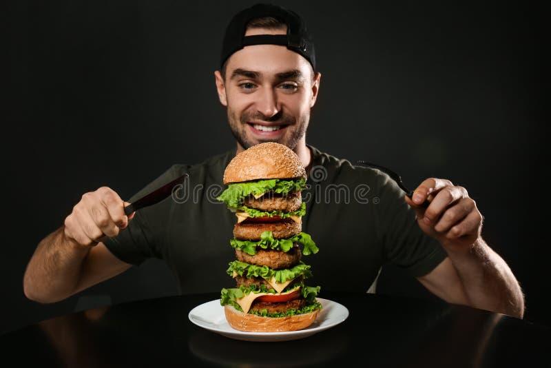 有利器的年轻人吃巨大的汉堡的 库存照片