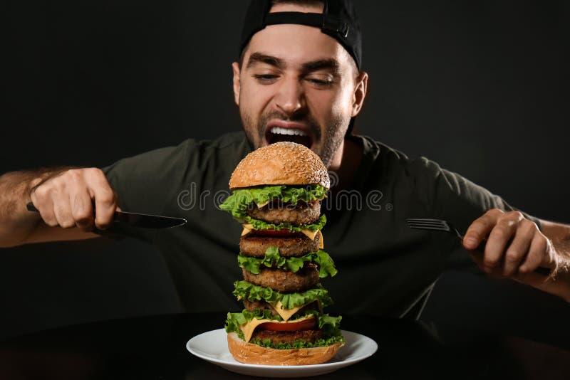 有利器的年轻饥饿的人吃巨大的汉堡的 免版税库存照片