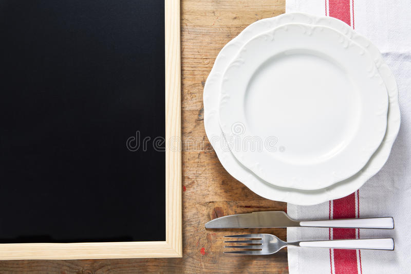 有利器的空的板材在木的背景和chal的黑色 免版税库存照片