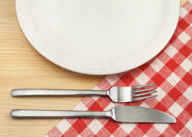 有利器的空的板材在木背景的红色方格的餐巾 免版税库存图片