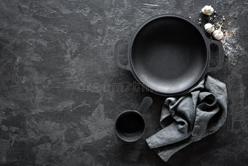 有利器的空的铸铁平底锅在餐馆菜单的黑暗的背景 免版税库存图片