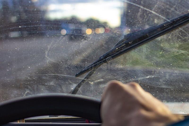 有刮水器的肮脏的被抓的汽车挡风玻璃通过被弄脏的方向盘用在被弄脏的背景的司机的手 图库摄影