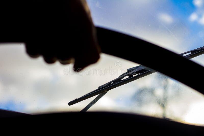 有刮水器的肮脏的被抓的汽车挡风玻璃通过被弄脏的方向盘用在被弄脏的背景的司机的手 免版税库存图片