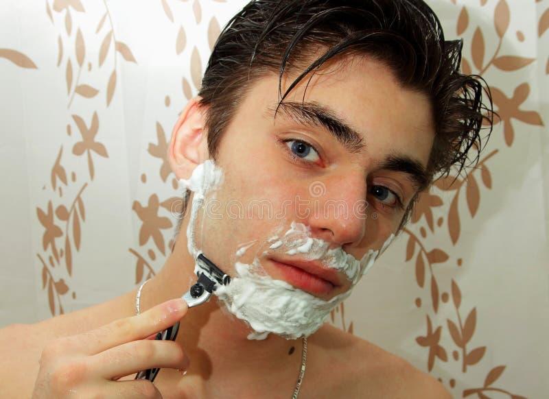 有刮的泡沫在他的面孔和一把剃刀人在他的手上 库存照片