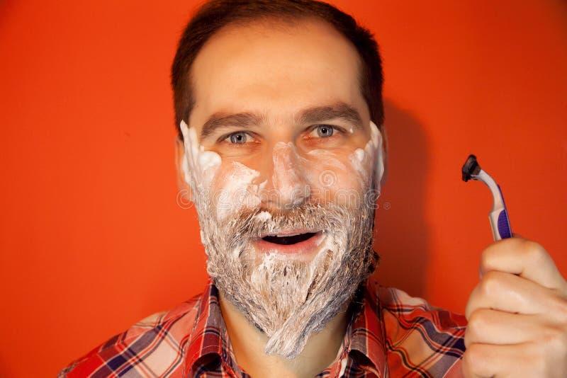 有刮的泡沫英俊的人在他的面孔和剃刀 免版税库存照片