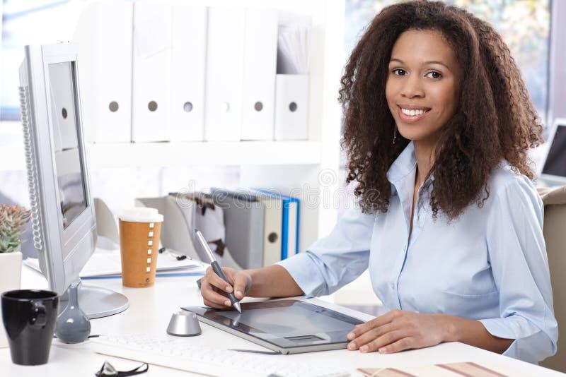 有制图桌的微笑的办公室工作者 免版税库存图片