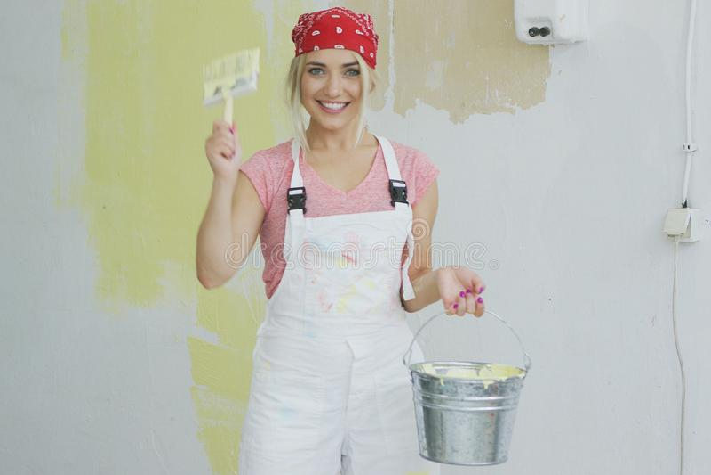 有刷子和油漆桶的高兴妇女 图库摄影