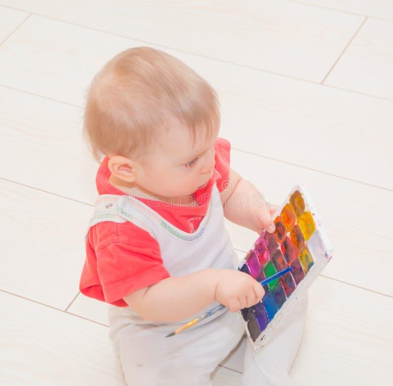 有刷子和油漆的一个婴孩 图库摄影