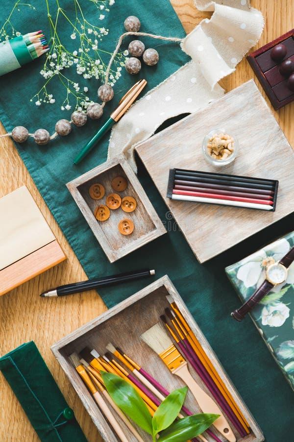 有刷子的在与绿色布料、鲜花和铅笔蜡笔的木桌安置的箱子和按钮在与大角度的照片 免版税库存照片