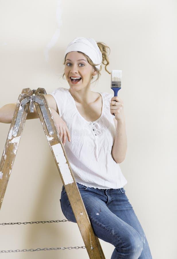 有刷子的妇女在梯子 免版税库存图片