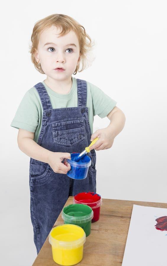 有刷子的小女孩在油漆木盆 库存照片