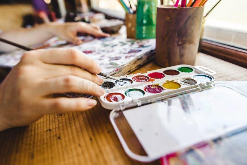 有刷子绘画的女孩手 图库摄影