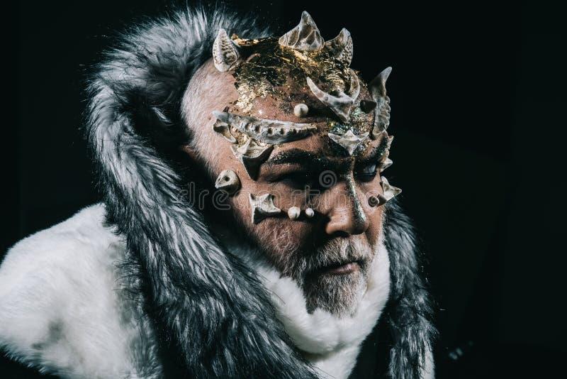 有刺和爬虫类皮肤佩带的白色毛皮大衣的妖怪在黑背景 从领土的邪魔监护人  库存图片