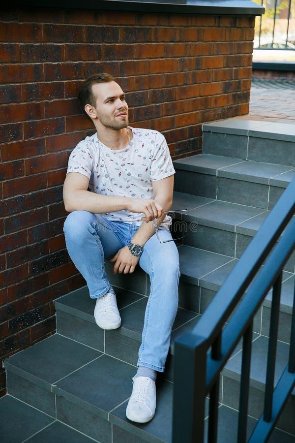有刺毛的一年轻帅哥坐花岗岩楼梯在一栋砖瓦房附近在一个夏天晚上 图库摄影