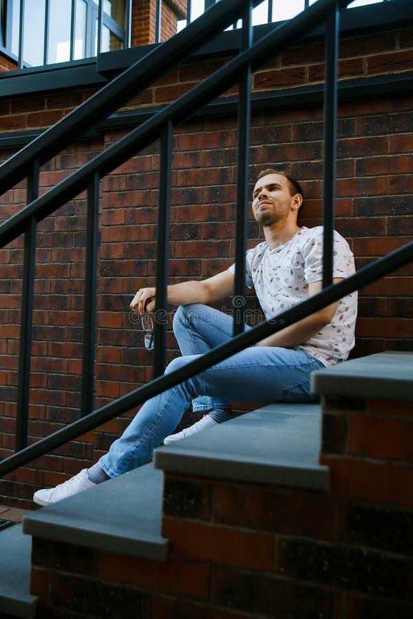 有刺毛的一年轻帅哥坐花岗岩楼梯在一栋砖瓦房附近在一个夏天晚上 库存照片