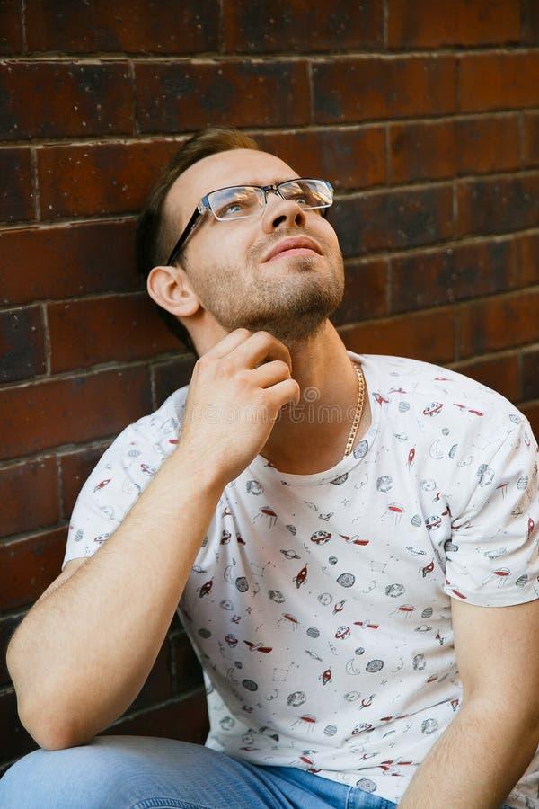 有刺毛的一年轻帅哥坐花岗岩楼梯在一栋砖瓦房附近在一个夏天晚上 免版税库存图片