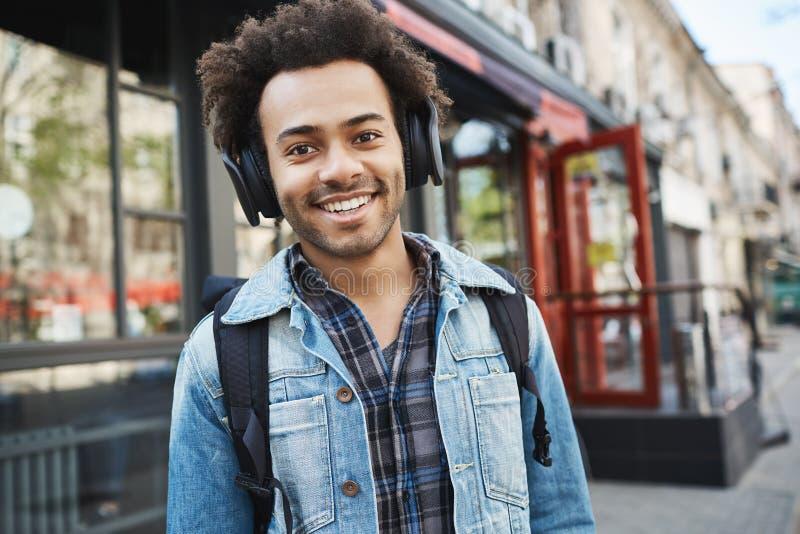 有刺毛的可爱的深色皮肤的微笑的人,听到音乐,当走在街道上,在好心情和时 免版税图库摄影