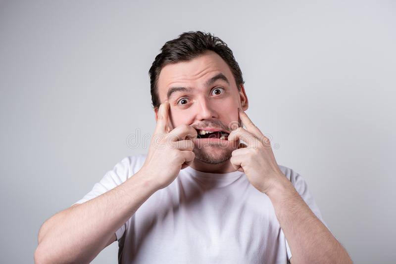 有刺毛的帅哥在白色T恤在他的面孔做滑稽的鬼脸 免版税库存照片