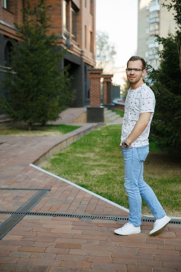 有刺毛的年轻美丽的时髦的人在一栋砖瓦房附近站立在一个夏天晚上 库存图片