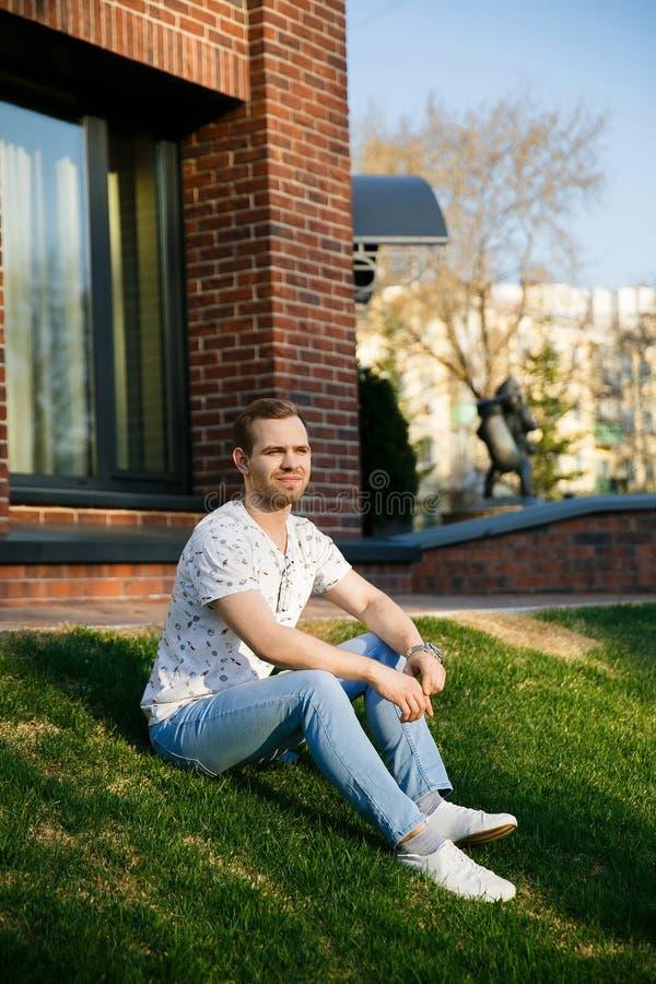 有刺毛的年轻美丽的时髦的人坐草坪在大厦附近在一个夏天晚上 图库摄影