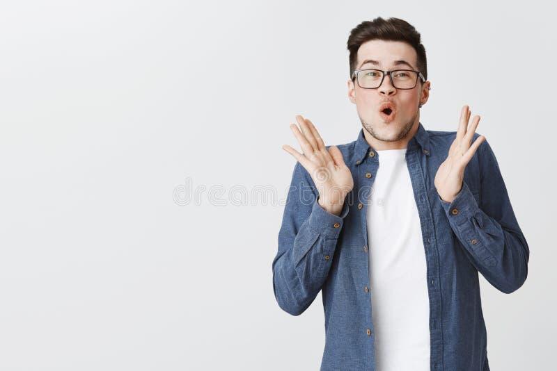 有刺毛的热心愉快和激动的年轻帅哥在举在喜悦的玻璃和蓝色衬衣手,拍手 免版税库存照片