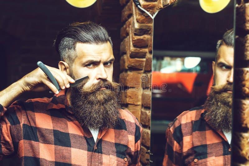 有剃刀的人在镜子附近 免版税库存照片