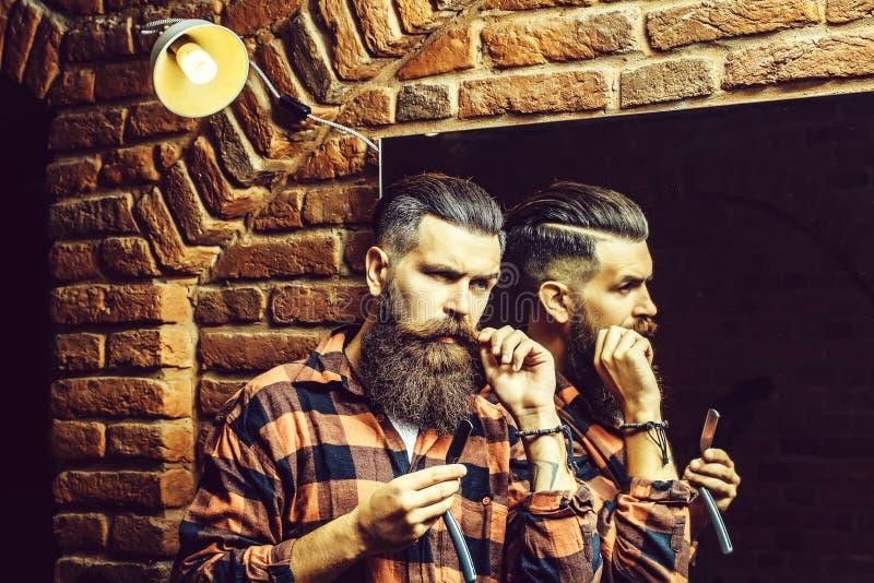 有剃刀的人在镜子附近 库存照片