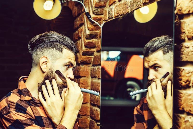 有剃刀的人在镜子附近 库存图片