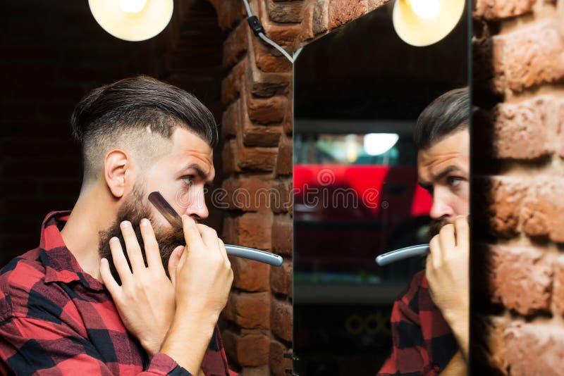 有剃刀的人在镜子附近 免版税库存图片
