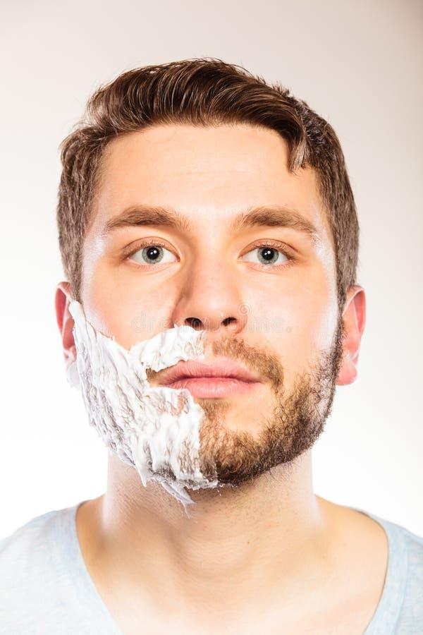有剃须膏泡沫的人在一半面孔 库存照片