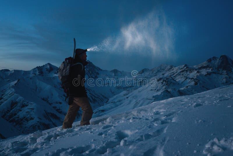 有前灯、背包和一个雪板的勇敢的人在他的后在多雪的山的后面攀登夜 人做在高土坎的滑雪游览 免版税库存照片