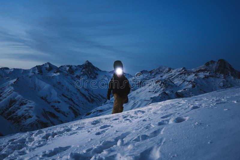 有前灯的勇敢的探险家承诺夜攀登给一座陡峭的多雪的山 佩带的滑雪穿戴和背包 Snowboar 库存图片