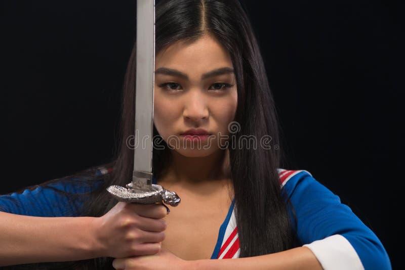 有剑的亚裔夫人在演播室 免版税图库摄影