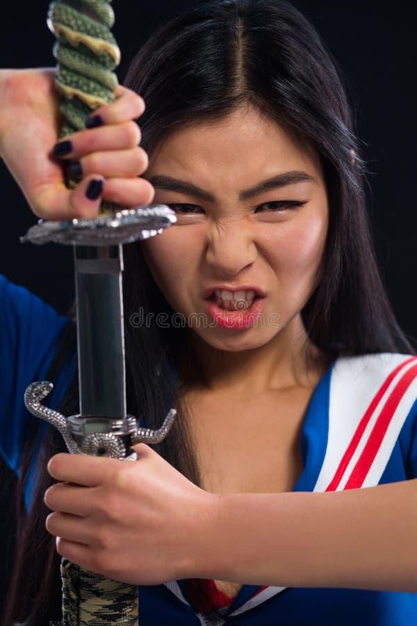 有剑的亚裔夫人在演播室 免版税库存图片