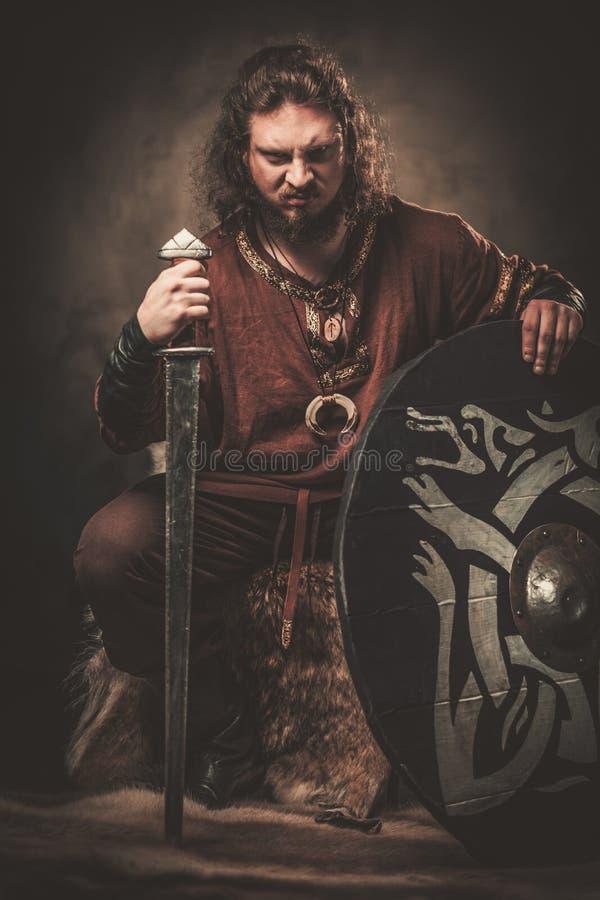 有剑的恼怒的北欧海盗在一个传统战士穿衣,摆在黑暗的背景 免版税库存照片