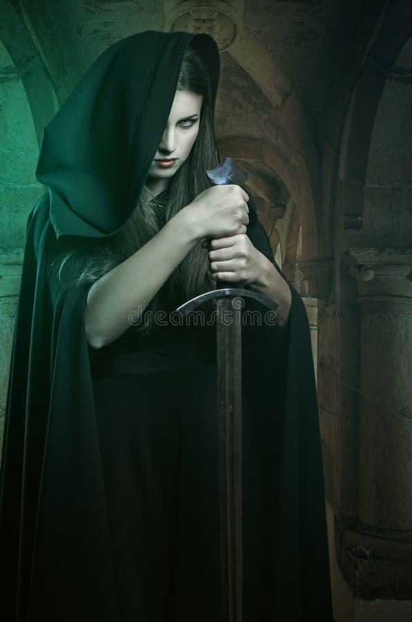 有剑的美丽的黑暗的妇女 免版税库存图片