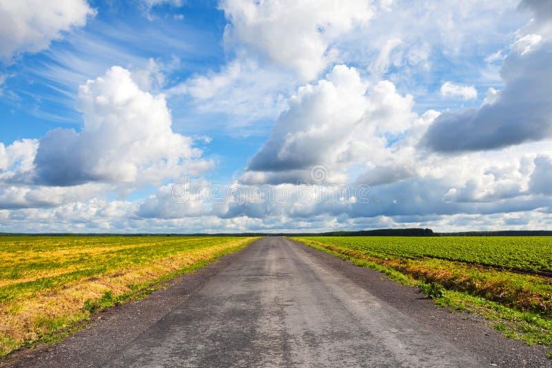 有剧烈的多云天空的空的沥青乡下公路 库存照片