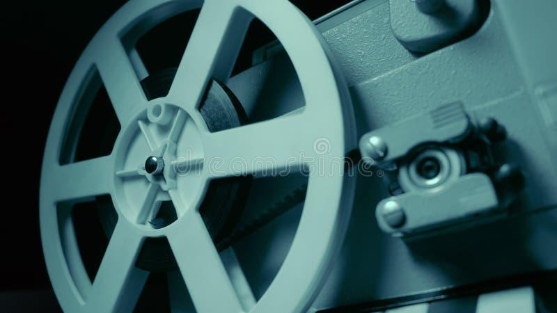 有剧烈的蓝色照明设备和选择聚焦的电影放映机 减速火箭的影片生产静物画 电影摄制的概念 免版税库存图片