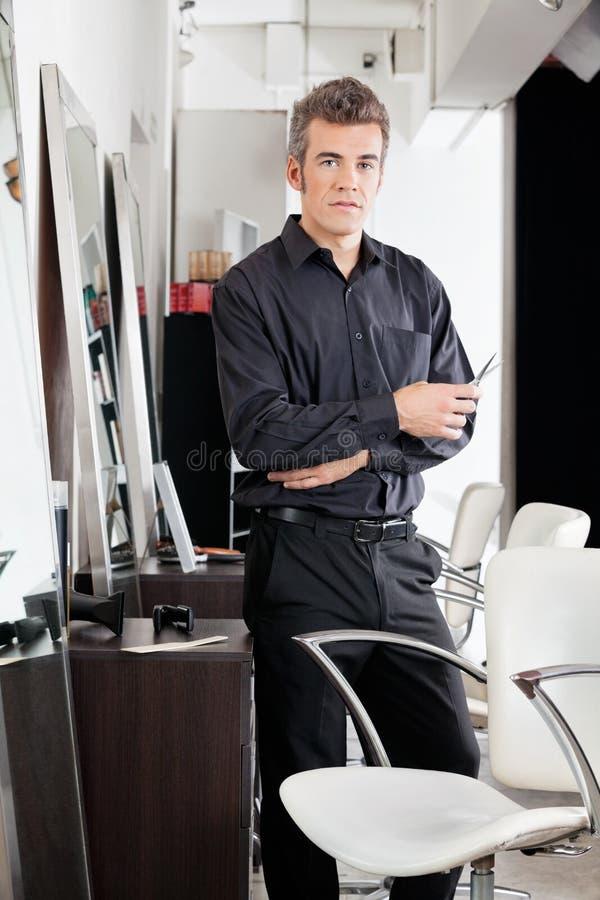 有剪刀的确信的男性美发师在沙龙 免版税库存照片