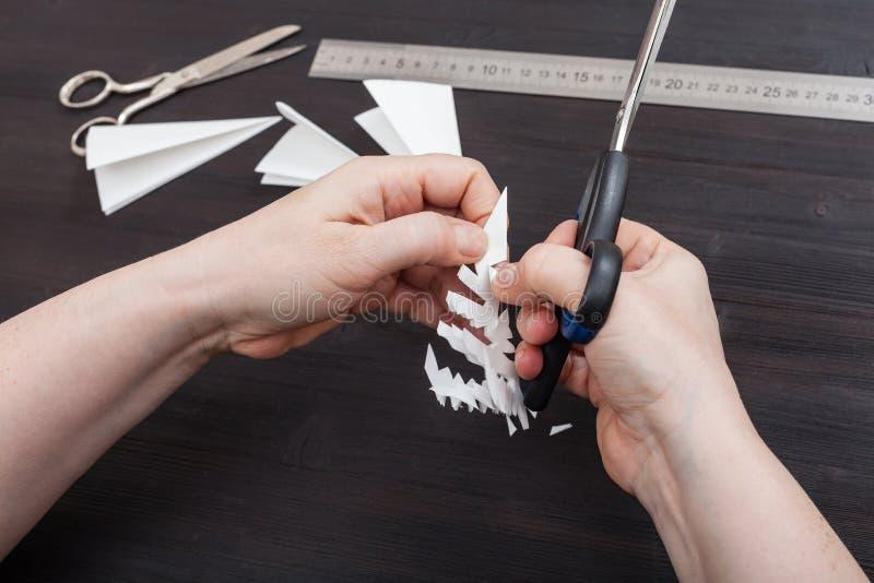 有剪刀裁减雪花的手从纸 免版税图库摄影