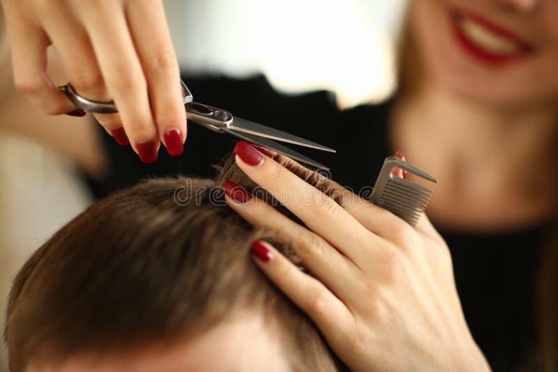有剪布朗男性头发的剪刀的美发师 免版税库存照片