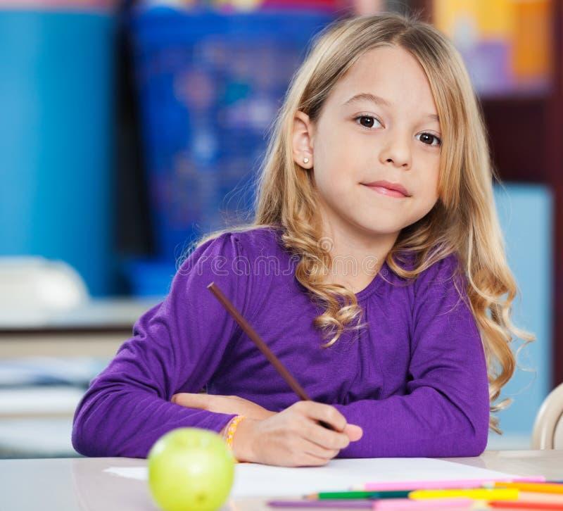 有剪影笔的逗人喜爱的在书桌的女孩和纸 库存图片