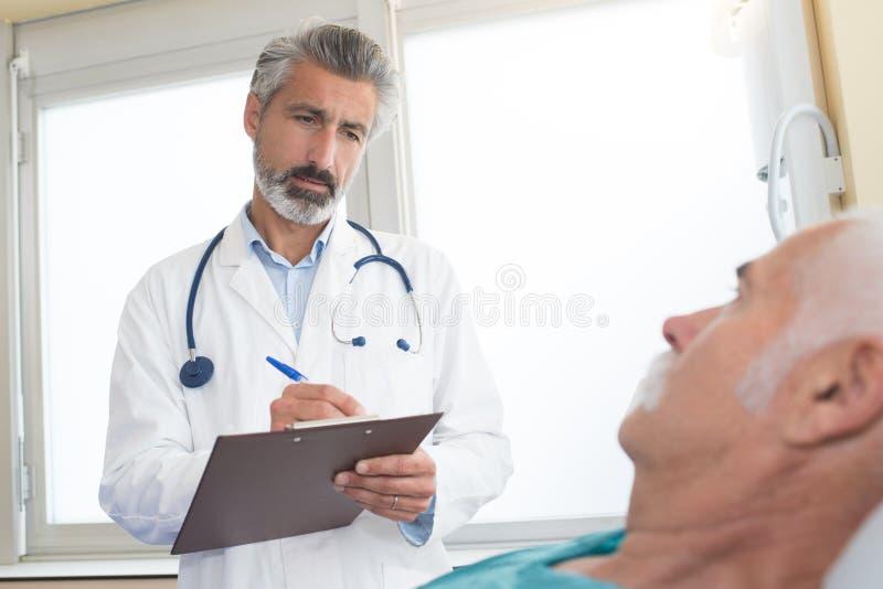 有剪贴板的医生拜访老人的在医院病房 图库摄影