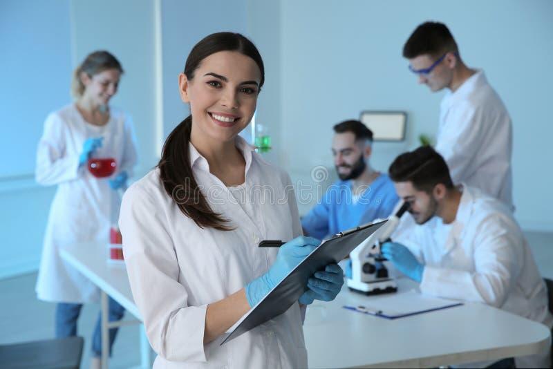 有剪贴板的医科学生在现代实验室 库存图片