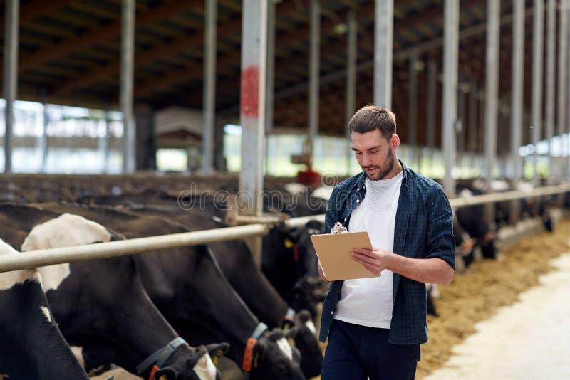 有剪贴板和母牛的农夫在农场的牛棚 库存照片