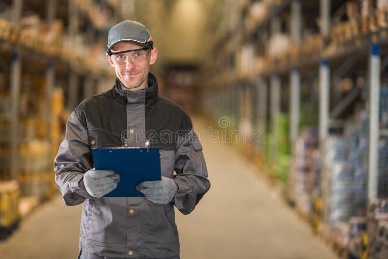 有剪贴板的微笑的白种人工作者在仓库里 免版税库存照片