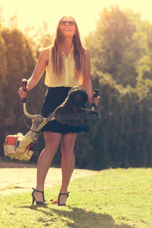 有割草机的女孩在公园 免版税库存照片