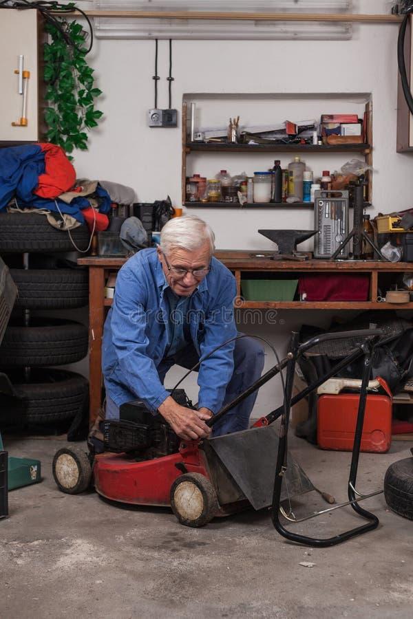 有割草机的资深工作者在车间 免版税库存照片
