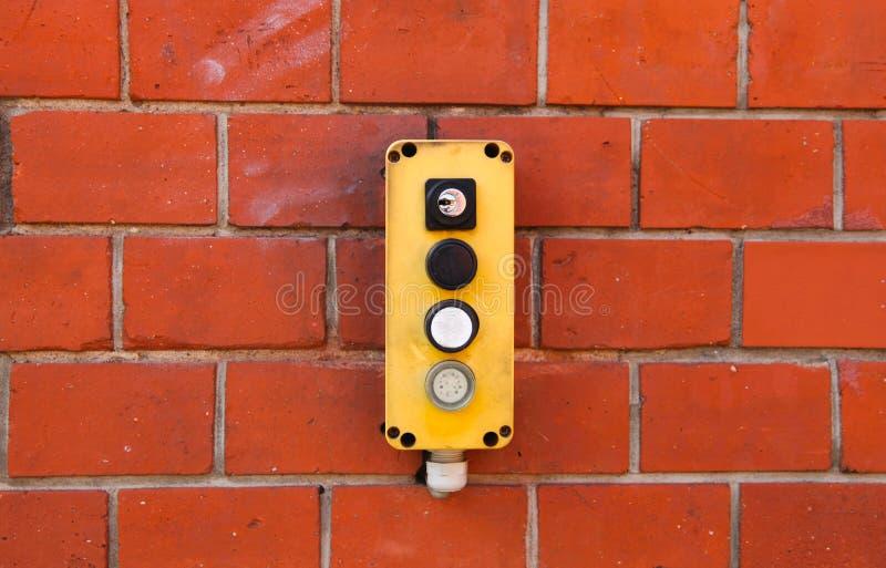 有力量的工业黄色开关盒开闭开关在从wareh的红砖墙壁和关键锁安装的户外按钮 图库摄影