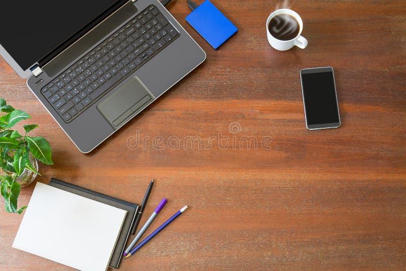 有办公用品、绿色植物和热的无奶咖啡的膝上型计算机与在葡萄酒难看的东西木书桌背景视图的烟从上面 免版税库存图片